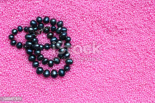 black pearl beads on pink background, copy space