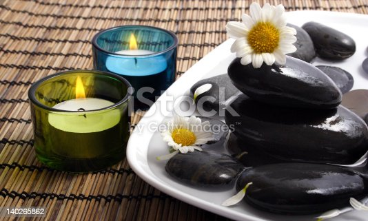 1175869940 istock photo Black pebbles and daisies in water 140265862