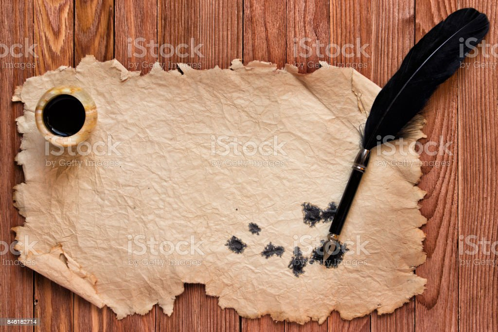 Black pen and ink on the background of old paper on a wooden table stock photo