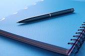 istock Black pen lies on blue notebook with documents 1321436001