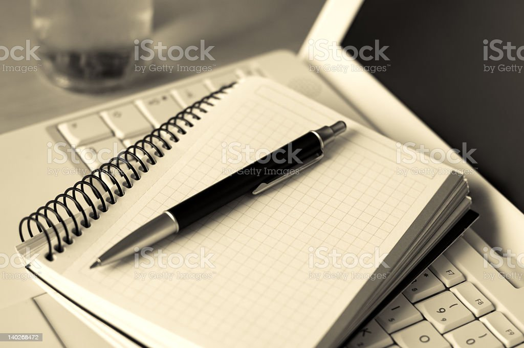 Black pen sitting on a notepad which is laying on a laptop stock photo