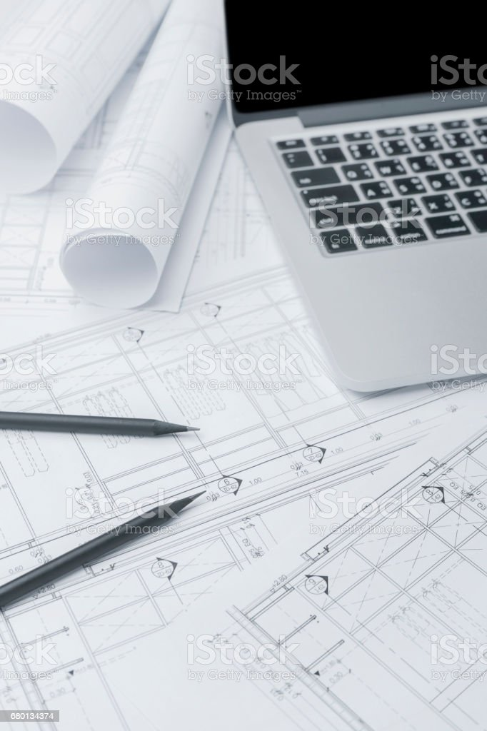 black pencil and computer laptop on architectural drawing paper for construction stock photo