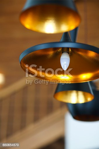 istock Black pendant lamp on ceiling wood wall 650654570