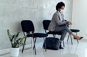 istock Black pensive businesswoman with face mask waiting for job interview. 1272461139
