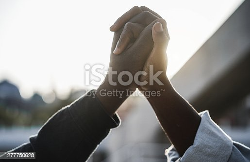 Black people holding hands during protest for no racism - Empowerment and equal rights concept