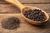 black pepper ground and grains on wooden background
