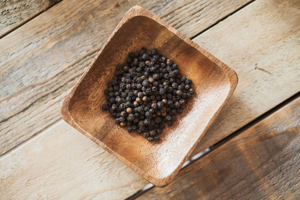 Black pepper in wood bowl shot from above stock photo