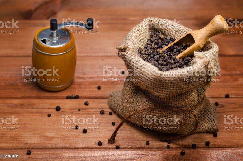 Petits pois poivre noir dans un sac et un moulin à poivre sur une table en bois photo libre de droits