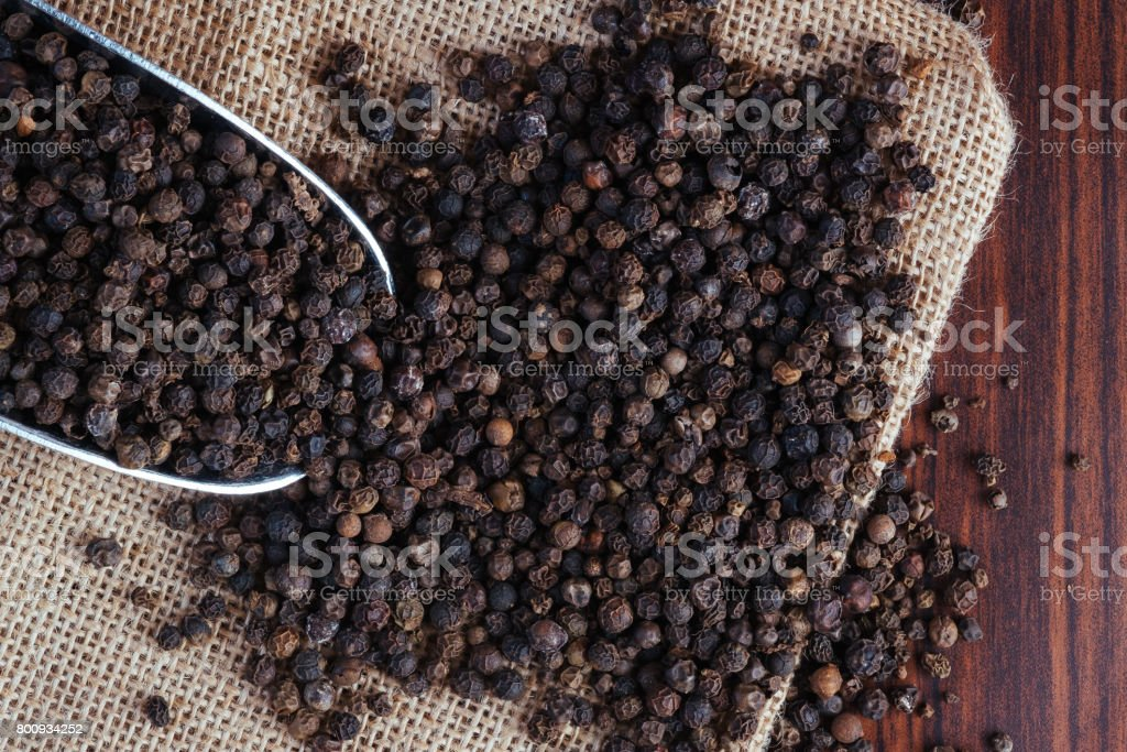 Black peppercorn top view on rustic sack stock photo
