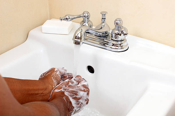 Black person washing with soap and water stock photo