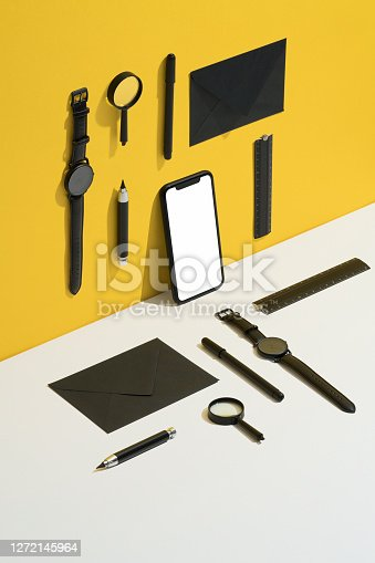 Black personal accessories, stationary flat lay with white screen smart phone on yellow and white background