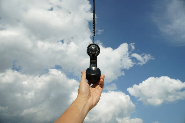 black phone with line hanging from the sky vintage black phone with line hanging from the sky. Conceptual photography talking to someone from above god talking stock pictures, royalty-free photos & images