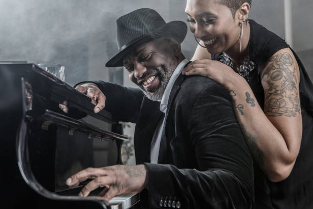 Black Piano Playing Man and beautiful Soul singer black woman stock photo