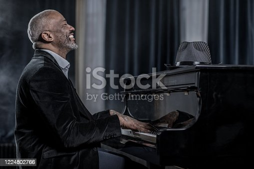 Black Gangster man playing the piano in a jazz club setting