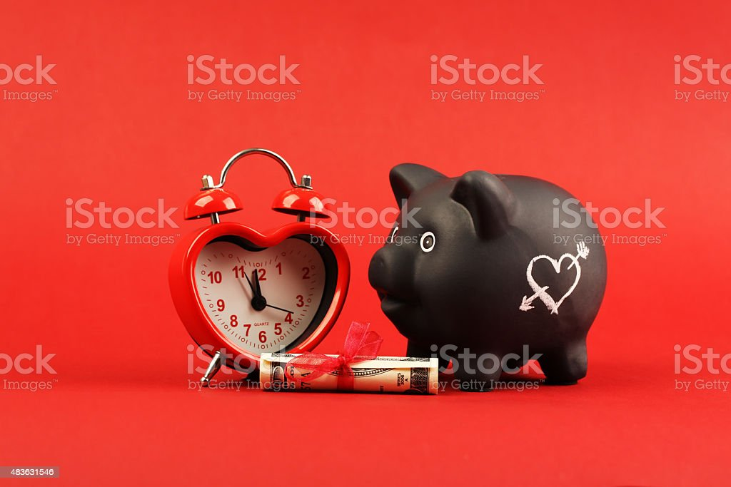 Black piggy bank with white heart and heart alarm clock stock photo