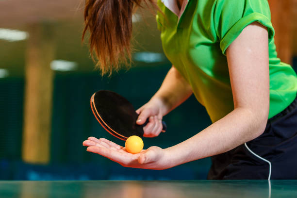 black ping pong paddle and ball in female hands close. serve the ball in table tennis - tenis stołowy zdjęcia i obrazy z banku zdjęć