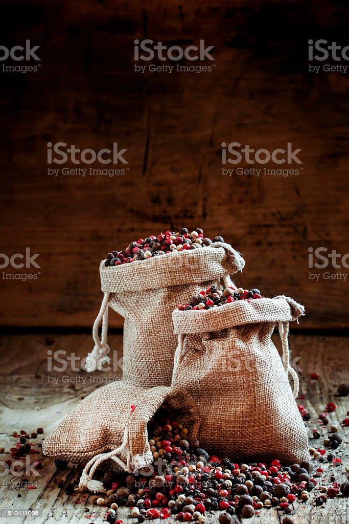 Black, pink, white pepper and allspice in burlap sacks stock photo