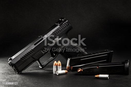 black pistol and cartridges on a dark background