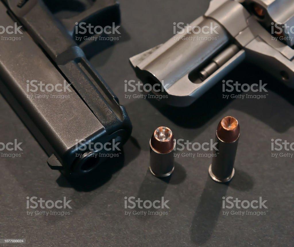 Una pistola negra con una punta hueca 40 calibre delante de él al lado de un revólver de acero inoxidable con una bala de punta hueca 357 calibre frente a ella - foto de stock