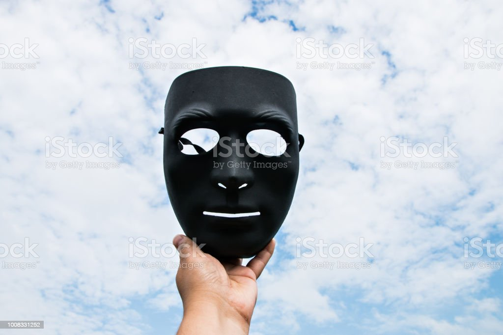 black plastic mask on blue sky background in hand stock photo