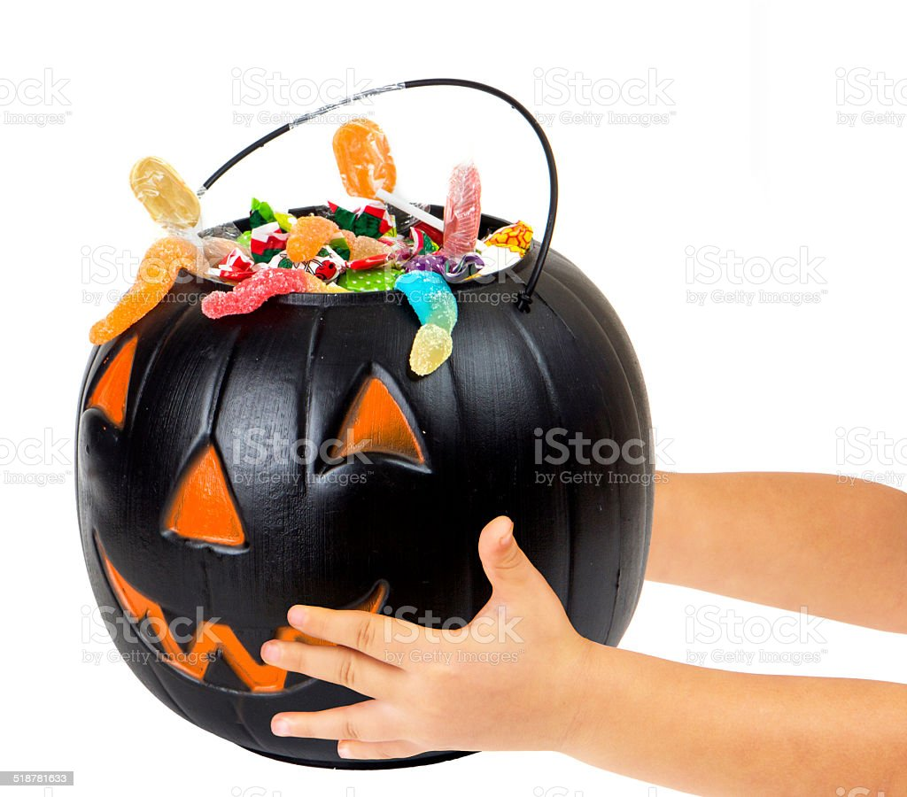 Black plastic pumpkin filled with candy and hand of kid stock photo