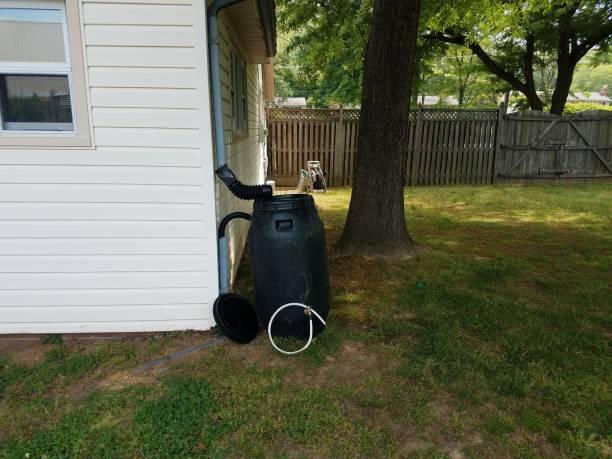 black plastic rain barrel installed on a house stock photo