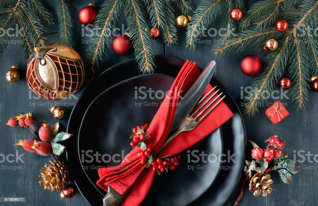 black plates and vintage cutlery with christmas decorations in green and red royalty free stock