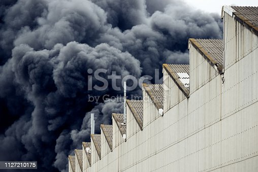 istock Black plumes of smoke from an accidental toxic industrial fire as seen from a behind a factory building. 1127210175