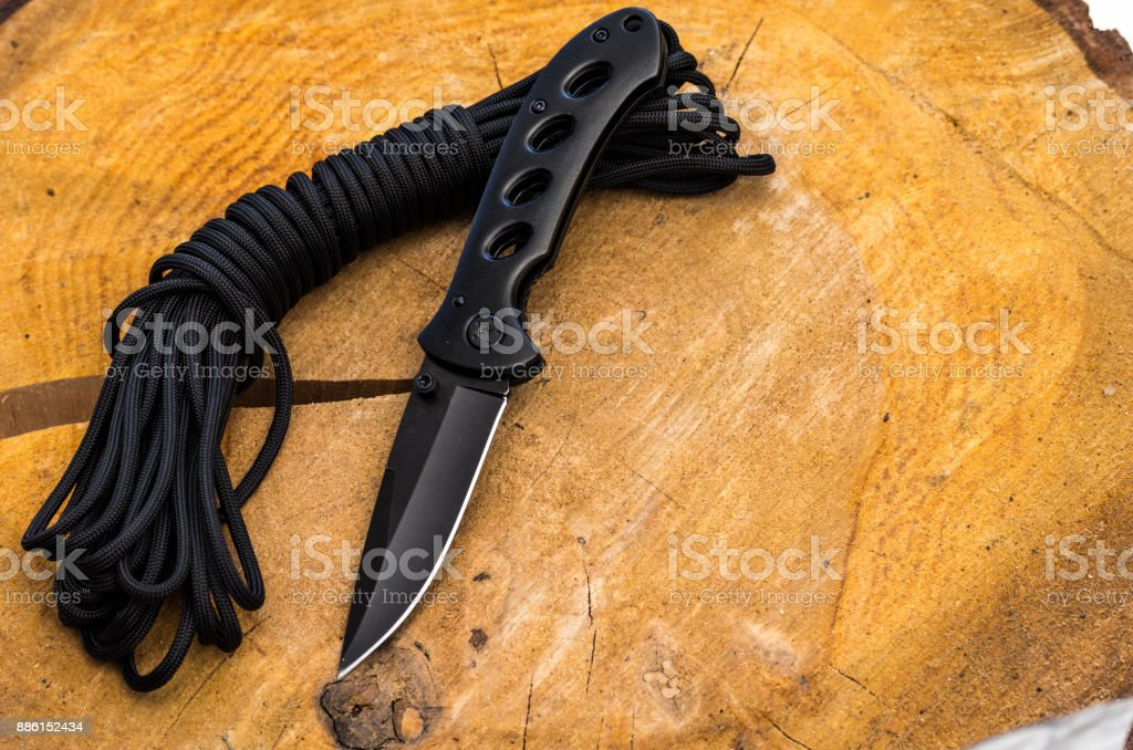 Black pocket knife and black parachute cord. stock photo