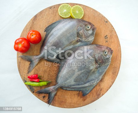Closeup view of Black Pomfret fish decorated with Vegetables and herbs on a wooden Pad,White Background.