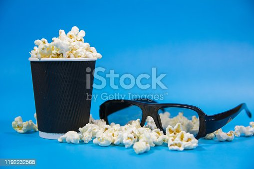 956942702 istock photo black popcorn box full of popcorn with spread popcorn and 3d black cinema glasses on vibrant blue background Film Movie background 1192232568