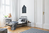 Black poster above bed with patterned sheets in white bedroom interior with plush toy. Real photo