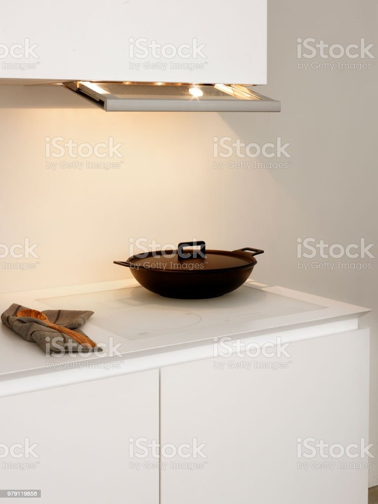 白いキッチンの白い誘導上黒鍋 ストックフォト