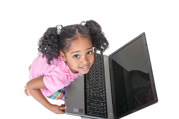 Black preschool girl with a laptop computer stock photo
