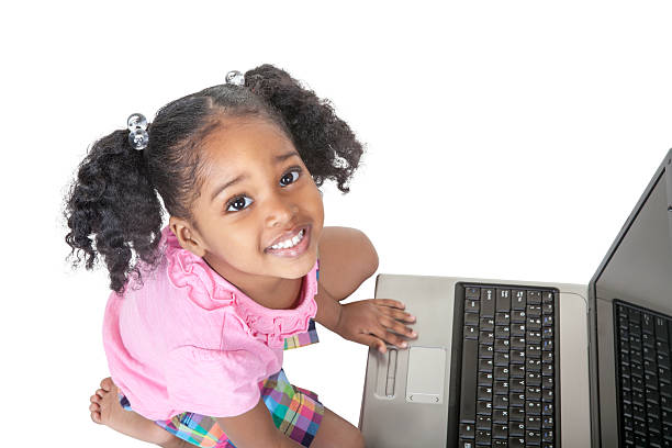 Black preschool girl with pigtails uses a laptop computer stock photo