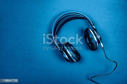 Top view of professional headphones on a  textured  background colored in blue. Copy space.Musical concept. Color of the year 2020.