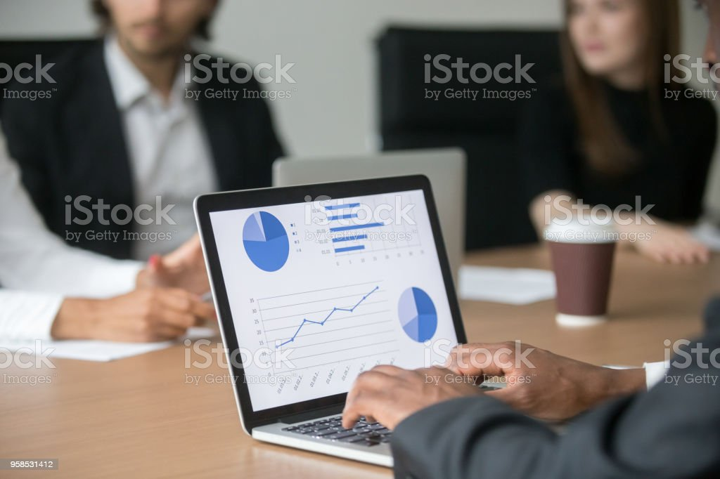Black project manager working on computer analyzing statistics at meeting stock photo