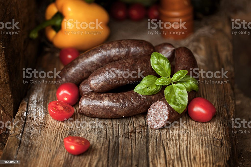 Black pudding, with cut slices, on chopping board . stock photo