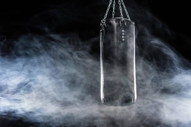 black punching bag - sandsäcke stock-fotos und bilder