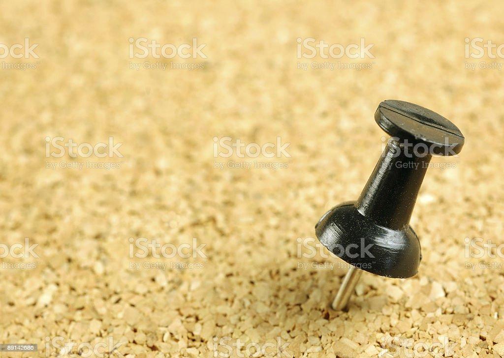 Black push-pin in corkboard royalty-free stock photo