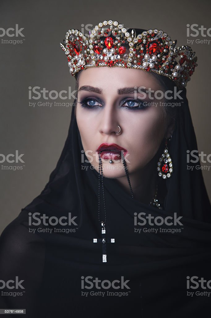 Black queen in a crown and with a crucifix stock photo