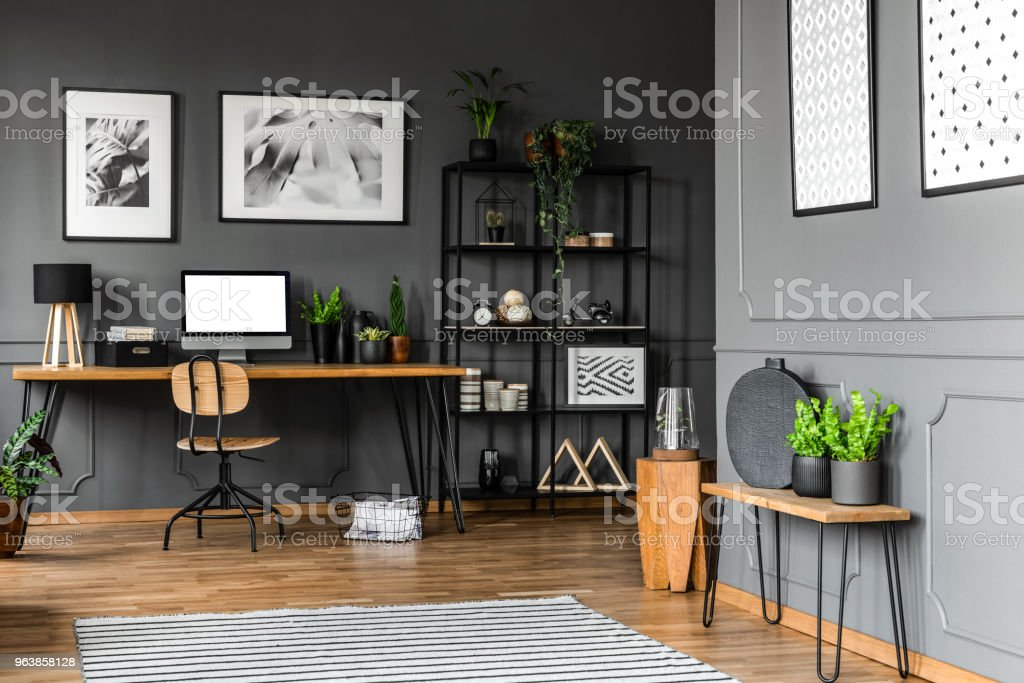 Black rack with decorations standing next to a wooden chair and desk with plants, lamp and a computer in home office interior. Real photo - Royalty-free Apartment Stock Photo