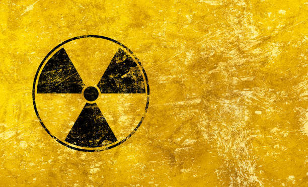 Black radioactive sign over yellow background Black radioactive hazard warning sign painted over grunge yellow background with copy space radioactive contamination stock pictures, royalty-free photos & images