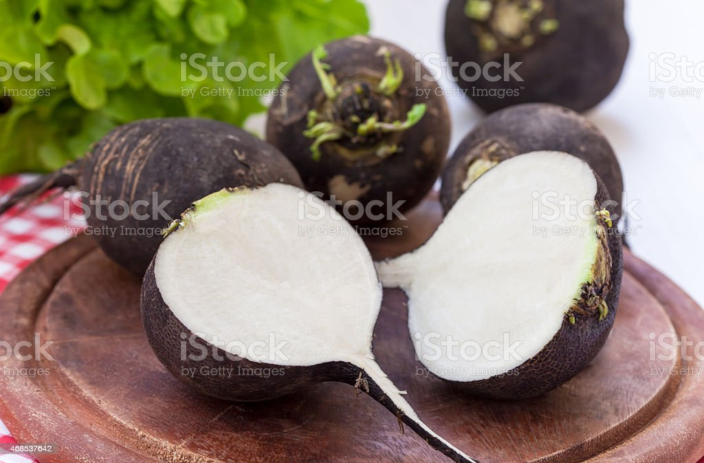 Black radish on wooden board stock photo