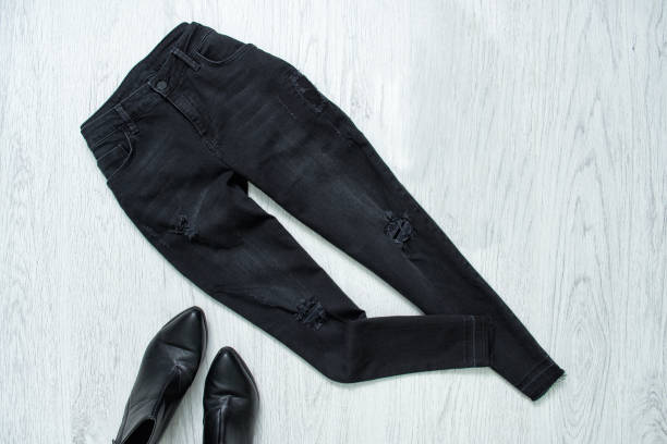 Black ragged jeans and black shoes on wooden background. Fashionable collage Black ragged jeans and black shoes on wooden background. Fashionable collage skinny jeans stock pictures, royalty-free photos & images