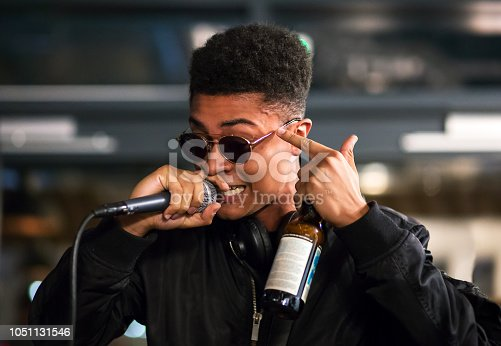 istock Black rapper performing with microphone, pointing to head. Bottle in hand. 1051131546