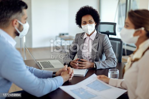 African American real estate agent talking to a couple while going through blueprints during the meeting. They are wearing protective face masks due to coronavirus pandemic.