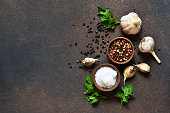 istock Black, red and white peppersalt, salt, garlic in a wooden bowl . Classic spices for cooking. View from above. 1132258583