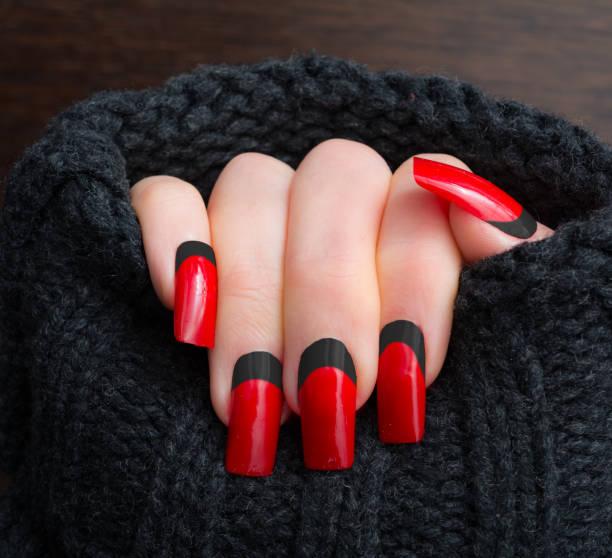 schwarz rot spitze nägel in warme strickjacke - nails stiletto stock-fotos und bilder