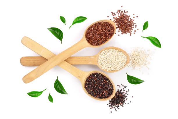 Graines de quinoa blanc rouge noir à la cuillère en bois décorée de feuilles vertes isolés sur fond blanc. Vue de dessus - Photo